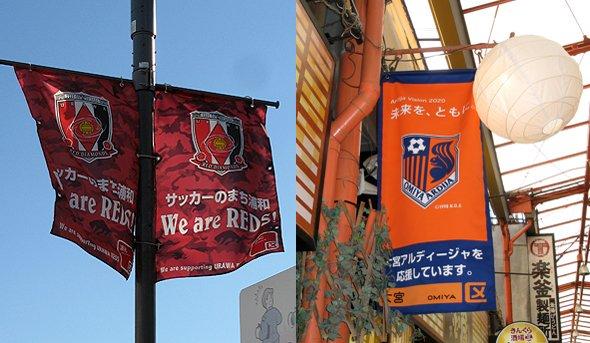 JR浦和駅前の街灯にかかる浦和レッズ応援旗(左)と、大宮駅東口すずらん通りにかかる大宮アルディージャ応援旗(右)
