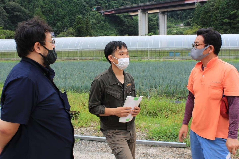 生産者の渡部さん(右)と話す、羽田さん(左)と寺嶋さん(中央)。寺嶋さんは、災害現場で活躍する探査機の研究経験も